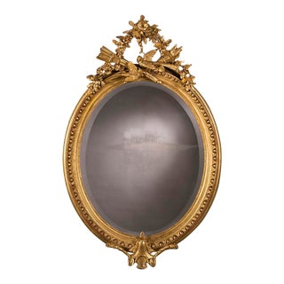 A grand Napoleon III style oval gold leaf frame from France c.1880 enclosing the original beveled mirror glass. (38″w x 57″h)