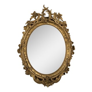 A sumptuous gilded oval frame enclosing the original beveled mirror glass from Belle Epoque period France c.1890 (32″w x 45″h)