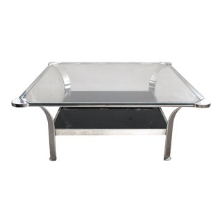 A large-scaled and shapely French 1970's steel square-form coffee table with clear glass top and black glass lower shelf