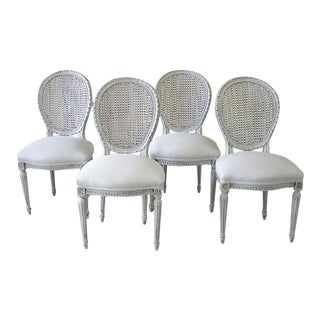 Louis XVI Carved and Painted French Cane Back Dining Chairs - Set of Four