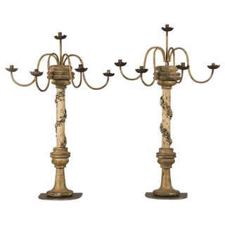 A pair of monumental painted wood candelabra each having five arms assembled from antique nineteenth century elements in Italy.