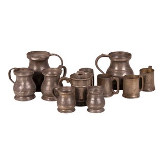 A set of eleven pewter cups and pitchers with various stamps from the makers from England c.1850