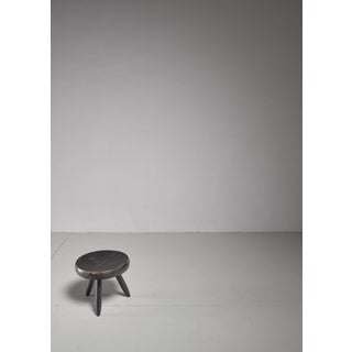 Charlotte Perriand low black stool, France, 1950s