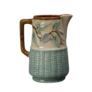 A lovely Barbotine glazed earthenware milk pitcher from France c. 1890 featuring a basketweave design enclosing the base enhanced with a floral spray