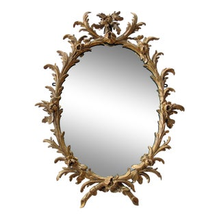 A good quality English George II rococo gilt-wood oval foliate-carved mirror