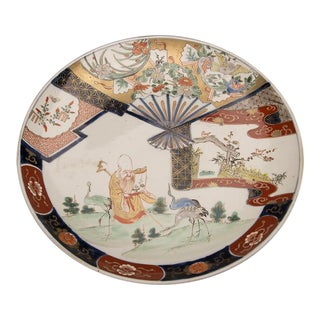 An Imari charger from Arita, Japan c. 1875 featuring a scholar reading a scroll in a landscape surrounded by three cranes