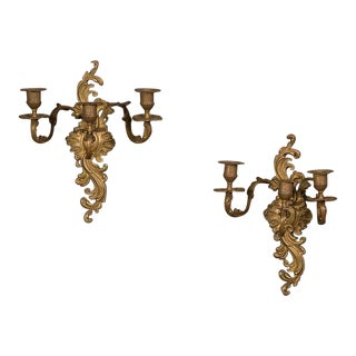 A pair of Louis XV style three-arm brass sconces in the Rococo taste from France c. 1895.
