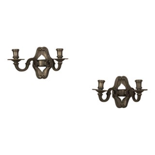 A pair of Régence style two-arm sconces with a dark bronze finish each having a shaped backplate from France c. 1900.