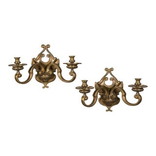 A pair of fanciful two-arm brass sconces having a shaped backplate from France c. 1920.