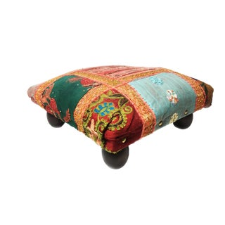 Vintage Moroccan foot stool with bright embellished boho fabrics and dark brown wood rounded legs.
