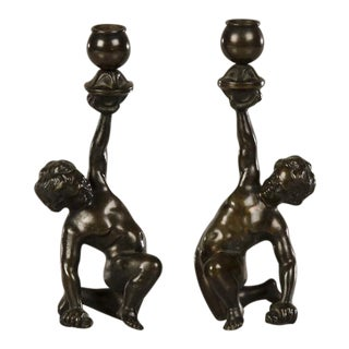 A pair of cast bronze candlesticks each featuring a kneeling putto from Italy c.1880