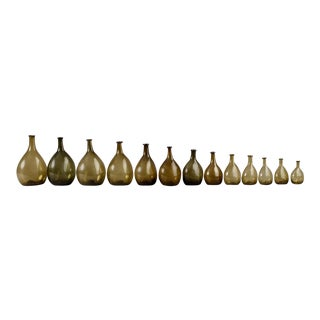 AN EXCEPTIONAL SET OF 13 GRADUATED BLOWN CHESTNUT BOTTLES